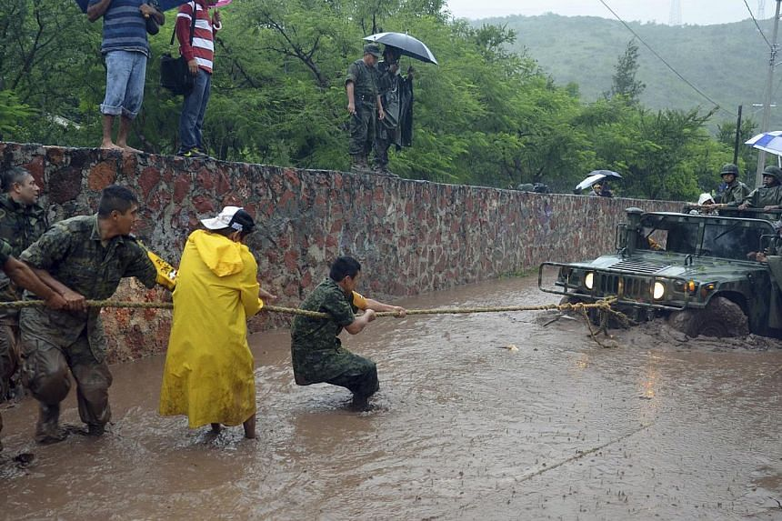 Army soldiers work to try to get their vehicle out of a flooded portion of a road caused by Tropical Storm Manuel in the city of Chilpancingo, Mexico, Sunday Sept 15, 2013. -- PHOTO: AP