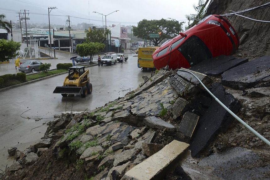 A car lies on its side after a portion of a hill collapsed due to heavy rains in the Pacific resort city of Acapulco, Mexico, Sunday, Sept 15, 2013. -- PHOTO: AP