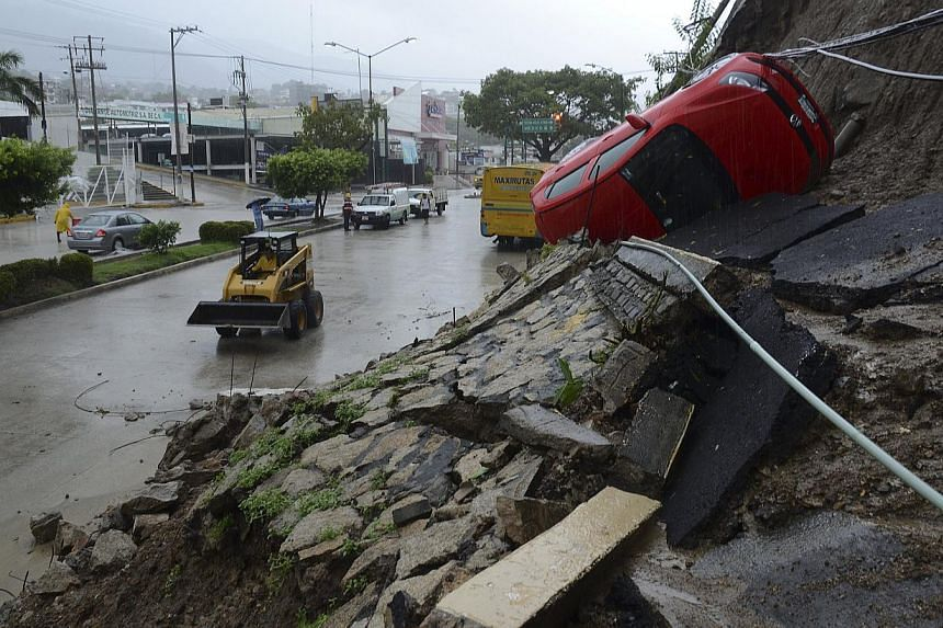 A car lies on its side after a portion of a hill collapsed due to heavy rains in the Pacific resort city of Acapulco, Mexico, on Sunday, Sept 15, 2013. Authorities scrambled to rescue people stranded in flooded homes in Mexico's resort of Acapul