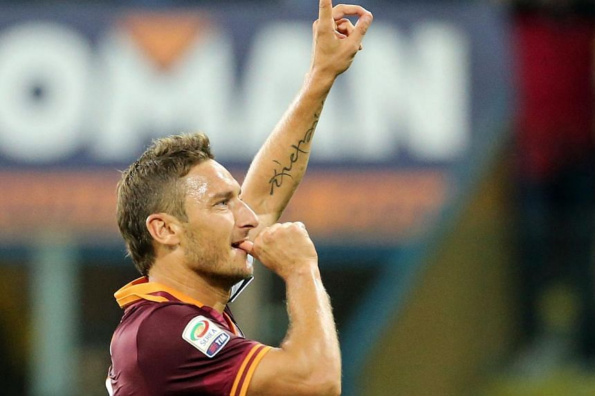 As Roma's captain Francesco Totti celebrates after scoring during the Serie A football match AS Roma vs Parma at the Tardini stadium in Parma on Sept16, 2013. Goals from Alessandro Florenzi, Francesco Totti and Kevin Strootman, from the penalty spot,