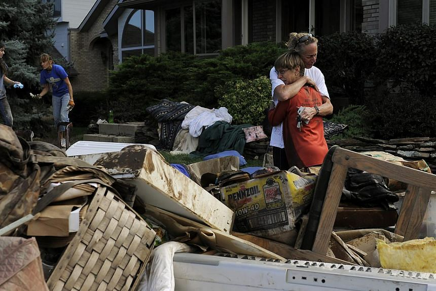 Homeowner Chris Ringdahl, right, is comforted by family friend Hillari Hansen, left, in front of her possessions as they cleanup from the floodwaters in Longmont, Colo., on Monday, Sept 16, 2013. The confirmed death toll from massive floods in the US