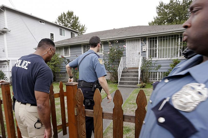 Seattle police officers walk toward a home where Aaron Alexis, the man identified as the shooter in the Washington Navy Yard shootings, has a connection with on Monday, Sept 16, 2013, in Seattle. US authorities probing the shooting spree at Washingto