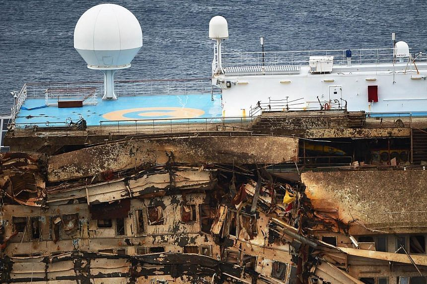 The wreck of Italy's Costa Concordia cruise ship emerges from water near the harbour of Giglio Porto on Tuesday, Sept 17, 2013. See more pictures from around the world in Through The Lens' Today In Pictures.-- PHOTO: AFP