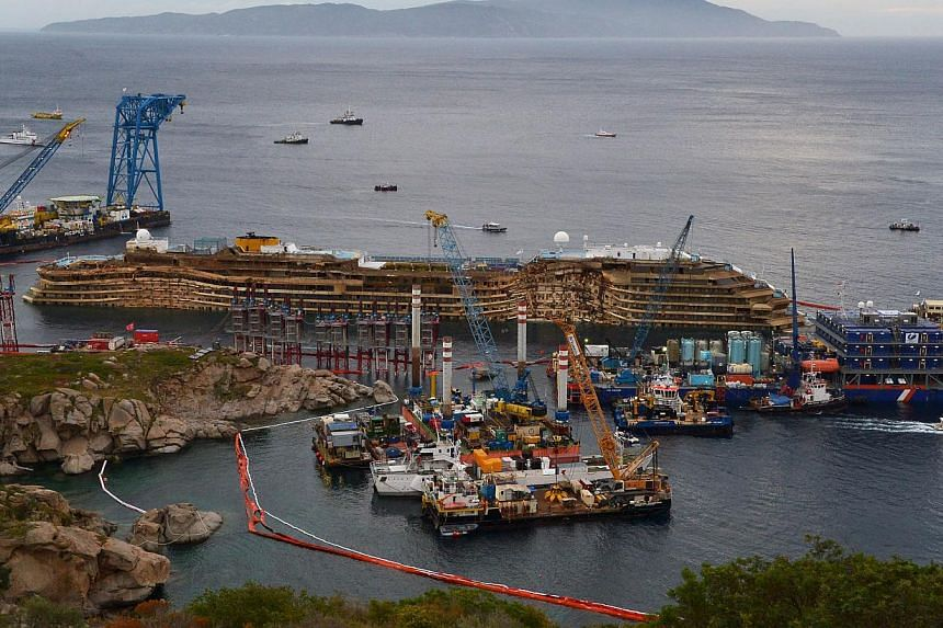 The wreckage of Italy's Costa Concordia cruise ship begins to emerge from water near the harbour of Giglio Porto on Tuesday, Sept 17, 2013. -- PHOTO: AFP