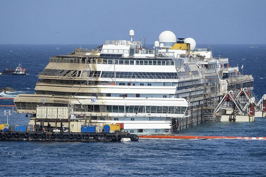 The wreckage of Italy's Costa Concordia cruise ship begins to emerge from water near the harbour of Giglio Porto on Tuesday, Sept 17, 2013. Salvage operators in Italy lifted the Costa Concordia cruise ship upright from its watery grave off the island