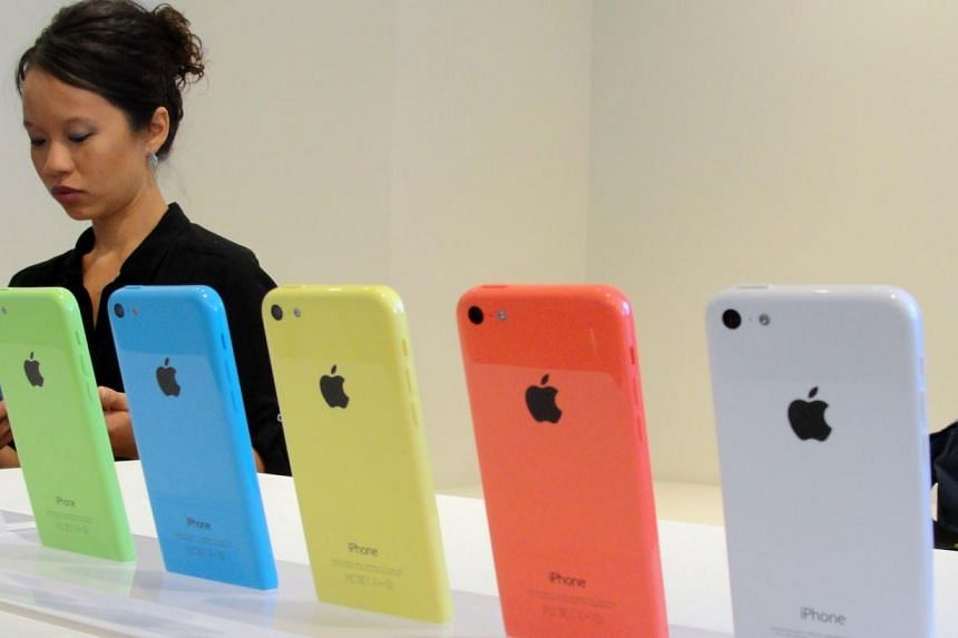 """The new """"low-cost"""" iPhone 5C at an iPhone event at Apple's headquarters in Silicon Valley on Sept 10, 2013, in Cupertino, California. SingTel announced price plans for the iPhone 5C and iPhone 5S, Apple'slatest flagship smartphone, on Tuesday,"""