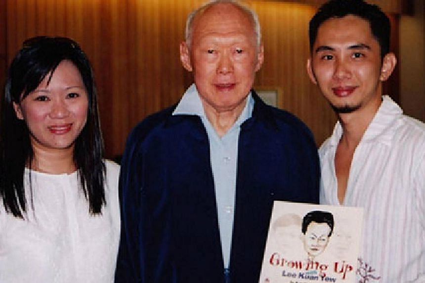 Mr Lawrence Koh Choon Teck (right) and his wife, Elina Ng, with Mr Lee Kuan Yew in 2004. Mr Koh is holding a copy of Growing Up With Lee Kuan Yew, a book he had illustrated and authored in 2000. -- PHOTO: LAWRENCE KOH CHOON TECK