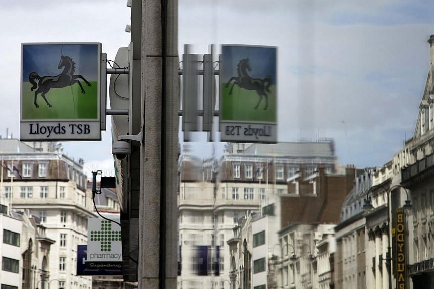 A Lloyds Bank sign is seen reflected in a window in central London on May 13, 2013.The British government earned 3.2 billion pounds (S$6.4 billion) from selling 6 per cent of Lloyds Banking Group, it announced on Tuesday, Sept 17, 2013, p