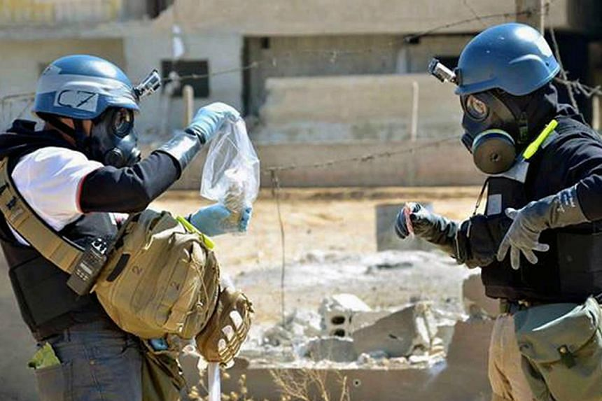 In this Aug. 28, 2013, citizen journalism image provided by the United Media Office of Arbeen which has been authenticated based on its contents and other AP reporting, members of the UN investigation team take samples from sand near a part of a miss