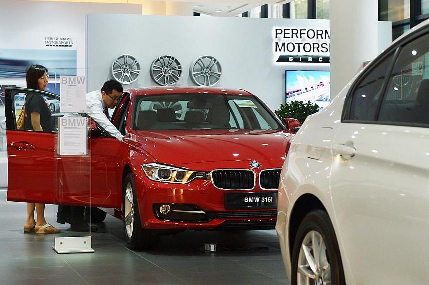 Customers look at a BMW 316i car at the Performance Motors showroom on Alexandra Road on Sept 9, 2013. Several parties have come out in opposition to the Government's decision to use engine power as a criterion for the certificate of entitlement (COE