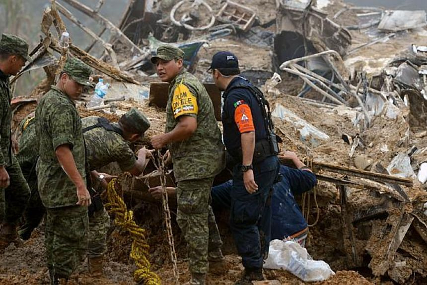 Mexican soldiers and police look for victims of a landslide caused by heavy rains in Xaltepec community, State of Veracruz, Mexico on Sept 16, 2013. -- PHOTO: AFP