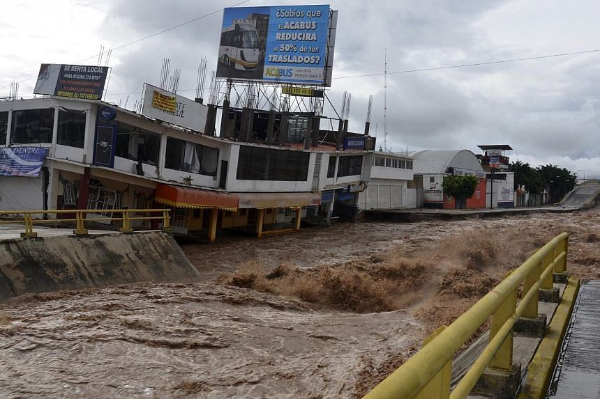 Floodwaters rage past an urban area after the Huacapa River overflowed due to heavy rains caused by Tropical Storm Manuel in Chilpancingo, Mexico, Monday, Sept 16, 2013. -- PHOTO: AP