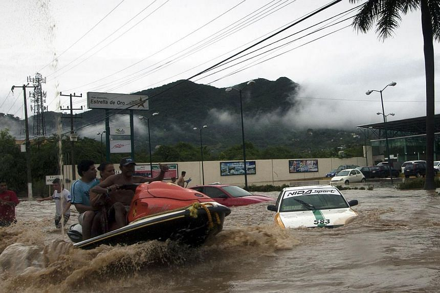 A man in a jet ski helps residents to leave the flooded area in Acapulco, Guerrero state, Mexico, after heavy rains hit the area on Septr 16, 2013. -- PHOTO: AFP