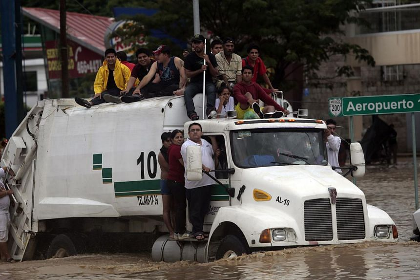 Residents attempt to leave the flooded area in Acapulco, Guerrero state, Mexico, after heavy rains hit the area on Sept 16, 2013. -- PHOTO: AFP