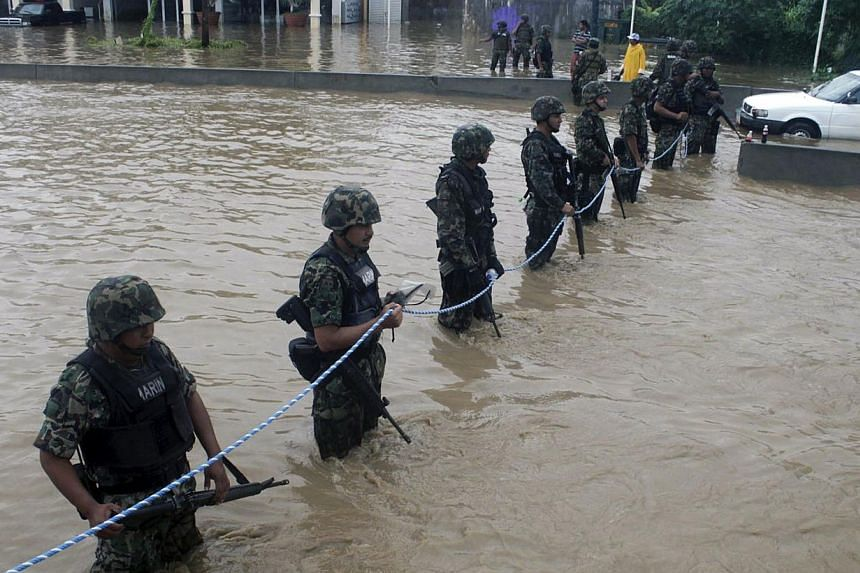 Mexican Navy members secure a flooded area to prevent theft and robbery in Acapulco, Guerrero state, Mexico, after heavy rains hit the area on Sept 16, 2013. -- PHOTO: AFP