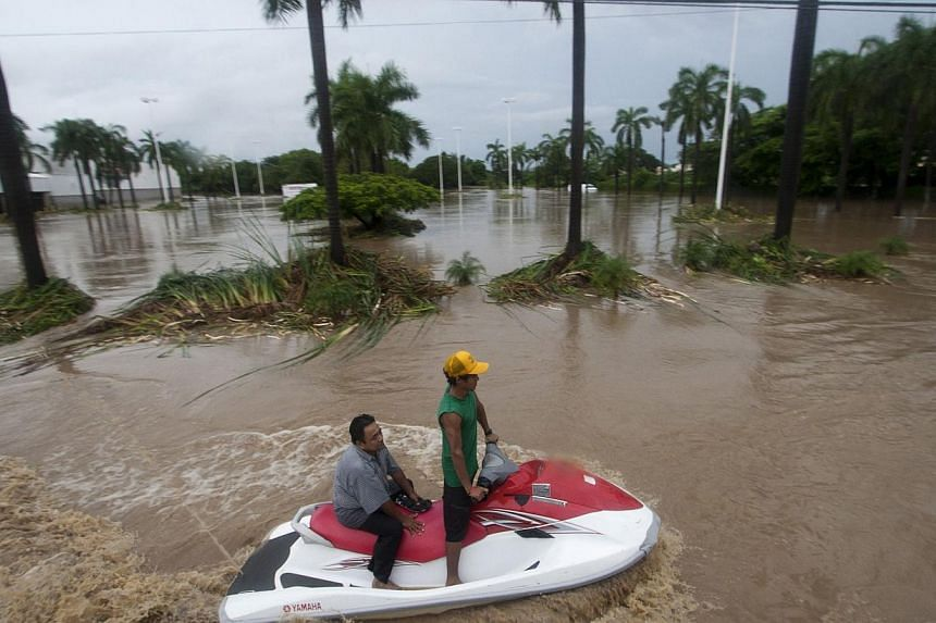A man with a jet ski helps residents to leave the flooded area in Acapulco, Guerrero state, Mexico, after heavy rains hit the area on Sept 16, 2013. -- PHOTO: AFP