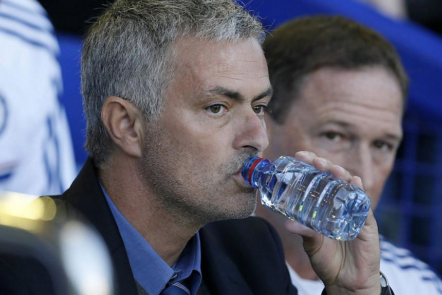 Chelsea manager Jose Mourinho drinks from a water bottle during their English Premier League football match against Everton at Goodison Park in Liverpool, northern England Sept 14, 2013. Mourinho is ready to erase one of the worst memories of h