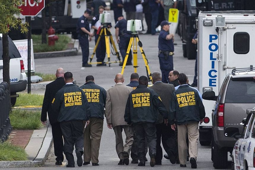 Police conduct an investigation into a shooting at the Navy Yard in Washington, DC, on Sept 16, 2013. A 34-year-old man opened fire at the Navy Yard on Monday in a shooting that left 13 people dead, including the gunman, not far from the US Capitol a