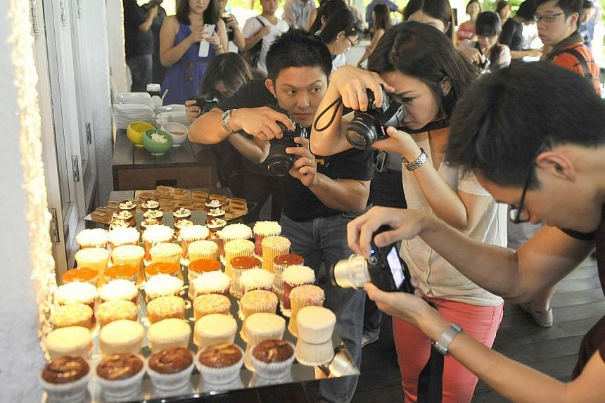 Photography enthusiasts taking photographs of a spread of food on July 28 2012.The popular habit of snapping photos of food has proved helpful in keeping diabetes in check. -- MY FILE PHOTO:JAMIE KOH