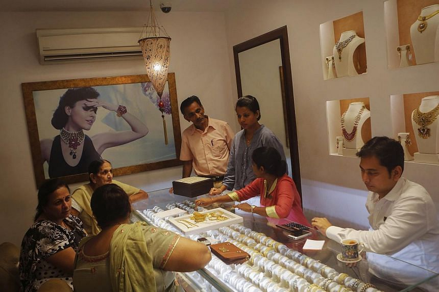 Customers shop inside a gold jewellery showroom in Mumbai Aug 30, 2013. India increased the import duty on gold jewellery to 15 per cent from 10 per cent on Tuesday, in a move aimed more at protecting the domestic jewellery industry rather than stemm