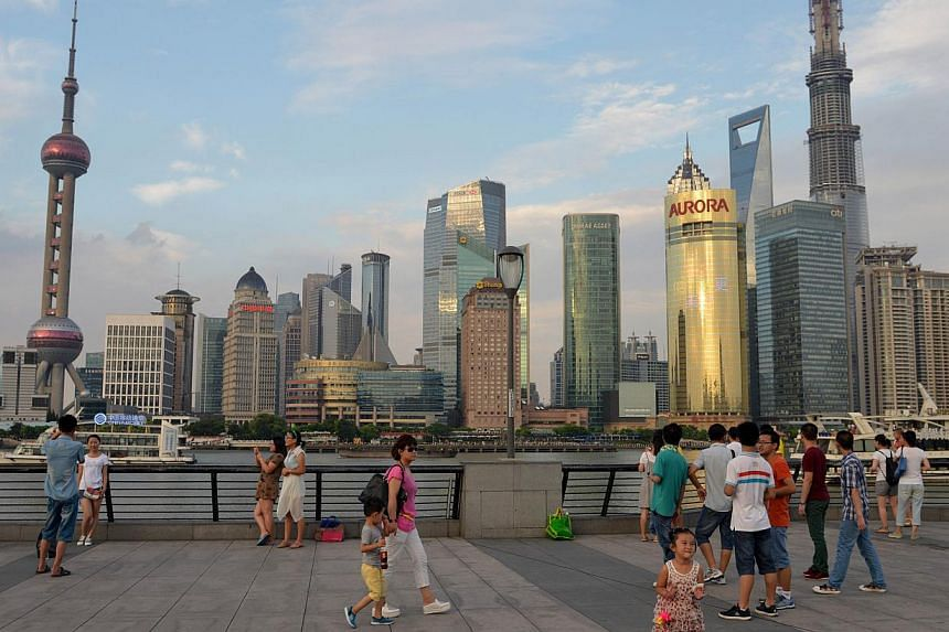 """People walking in front of the Shanghai skyline and the under construction Shanghai Tower on August 3, 2013. Asia's richest man Li Ka-shing warned that Shanghai's new free trade zone will have a """"big impact"""" on Hong Kong, urging the city to up its ga"""