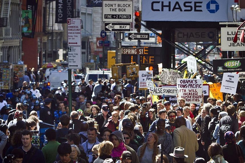 Scores of protesters representing the Occupy Wall Street movement, march along Broadway on Tuesday, Sept 17, 2013, in the Soho section of New York.Some 250 people gathered at midday in Zuccotti Park in Manhattan's downtown financial district, w