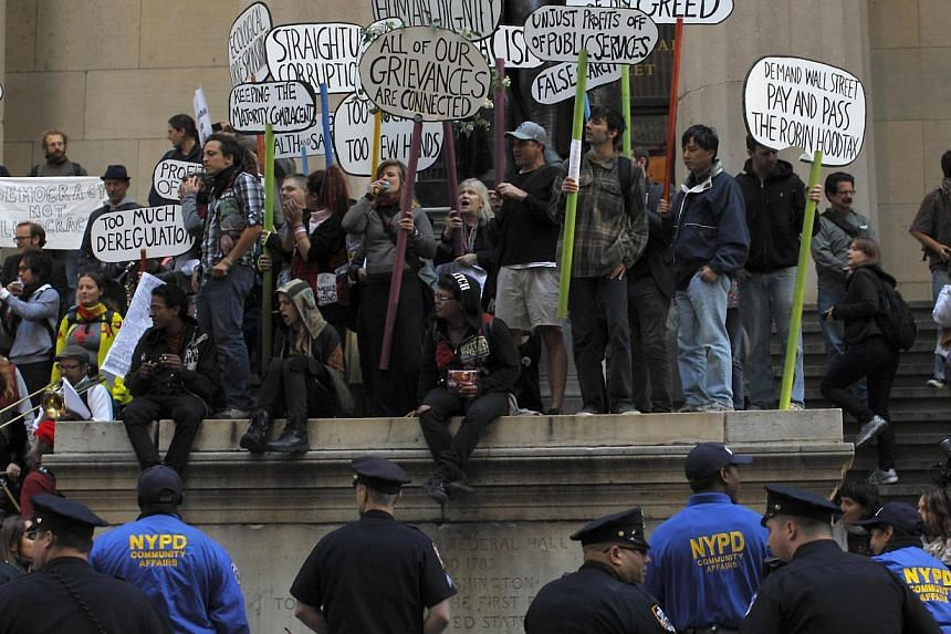 """Occupy Wall Street protesters stand on the steps of Federal Hall, across the street from the New York Stock Exchange in New York Sept 17, 2013.""""Occupy Wall Street"""" returned to the streets of New York Tuesday to mark the second anniversary of th"""