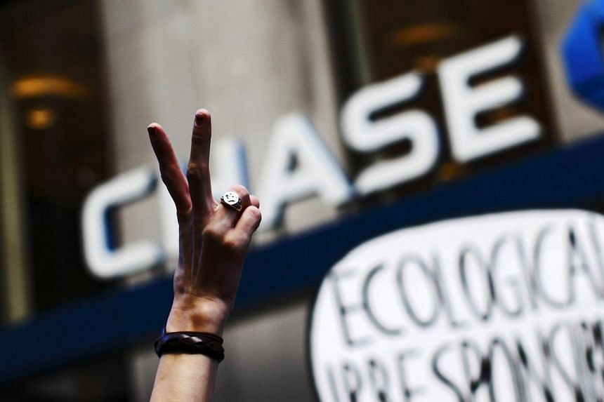 "An Occupy Wall Street protestor flashes a peace sign during a march on Broadway past a Chase bank in New York's financial district Sept 17, 2013.""Occupy Wall Street"" returned to the streets of New York on Tuesday to mark the second anniversary of the"