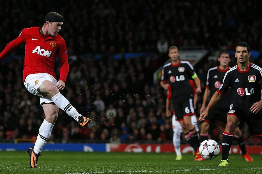 Manchester United's Wayne Rooney (left) shoots to score against Bayer Leverkusen during their Champions League soccer match at Old Trafford in Manchester, northern England September 17, 2013.Wayne Rooney reached 200 Manchester United goals with