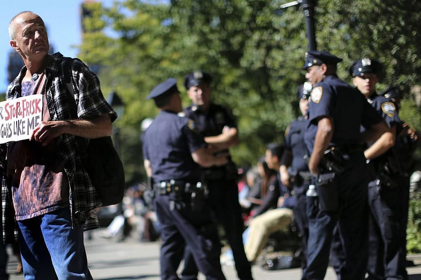 "A demonstrator associated with the Occupy Wall Street movement holding a sign referring to stop and frisk stands next to a group of police officers Tuesday, Sept 17, 2013 at Washington Square in New York. ""Occupy Wall Street"" returned to the str"