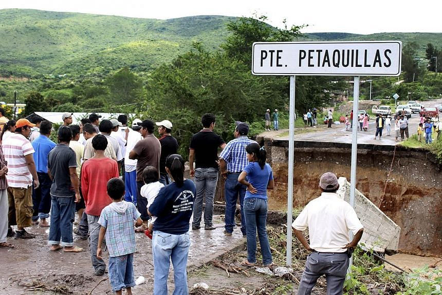 Residents stare at a bridge swept away by heavy rains in Chilpancingo, state of Guerrero, Mexico, on September 17, 2013.Mexican authorities scrambled Tuesday to launch an air lift to evacuate tens of thousands of tourists stranded amid floods i