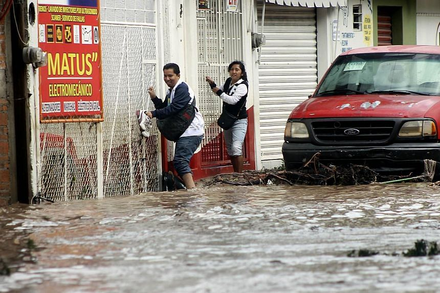 Residents attemp to cross a flooded street in Chilpancingo, state of Guerrero, Mexico, on September 17, 2013. Mexican authorities scrambled Tuesday to launch an air lift to evacuate tens of thousands of tourists stranded amid floods in the resort of