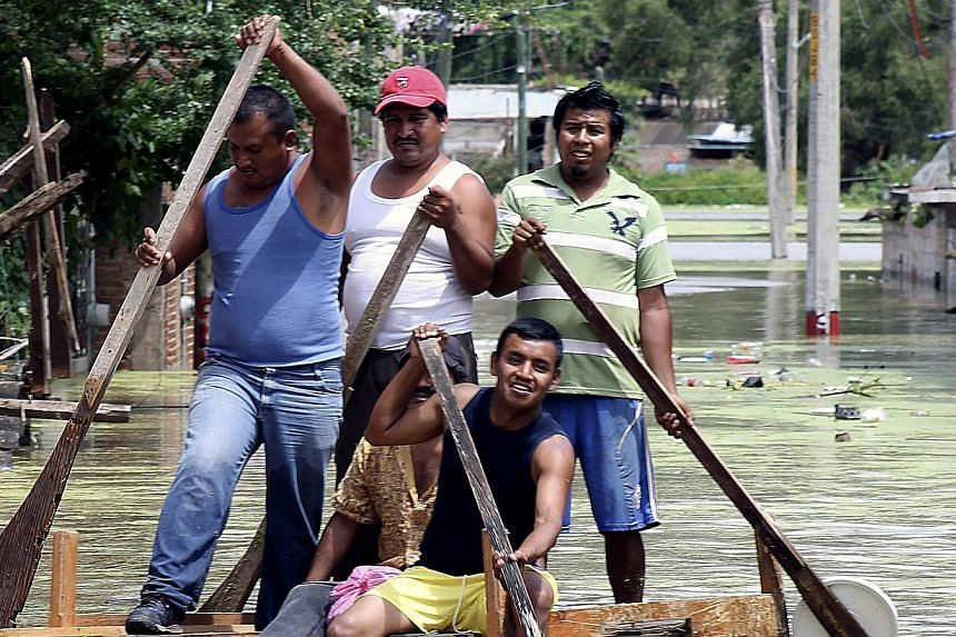 Residents attemp to cross a flooded street using a makeshift raft in Chilpancingo, state of Guerrero, Mexico, on September 17, 2013.State and local officials have reported 10 more deaths. -- PHOTO: AFP