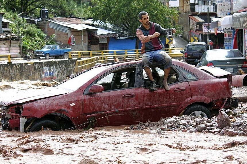 A man sits atop a car while trying to cross a flooded street in Chilpancingo, state of Guerrero, Mexico, on September 17, 2013.State and local officials have reported 10 more deaths. -- PHOTO: AFP