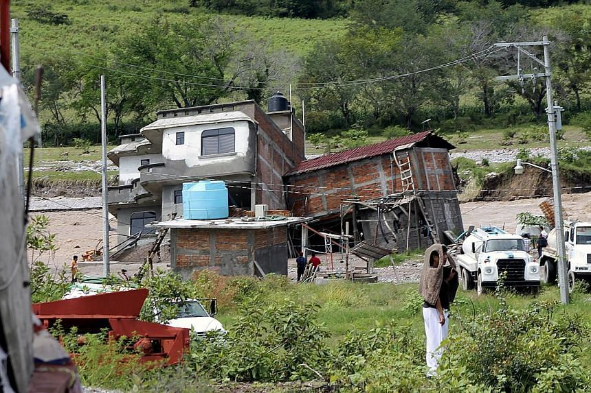 View of a damaged house in the banks of a river in Chilpancingo, state of Guerrero, Mexico, on September 17, 2013.Mexican authorities scrambled Tuesday to launch an air lift to evacuate tens of thousands of tourists stranded amid floods in the