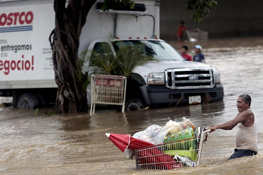 A man pulls a cart with supplies through a flooded street in Acapulco, state of Guerrero, Mexico, on September 17, 2013 as heavy rains hit the country.Mexican authorities scrambled Tuesday to launch an air lift to evacuate tens of thousands of