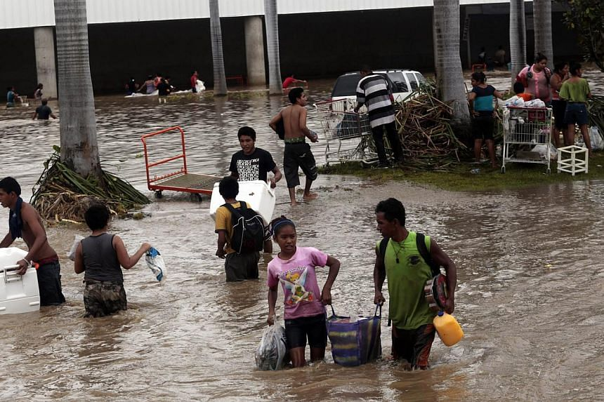 Residents carrying belongings wade through a flooded street in Acapulco, state of Guerrero, Mexico, after heavy rains hit the area on September 17, 2013.Mexican authorities scrambled Tuesday to launch an air lift to evacuate tens of thous