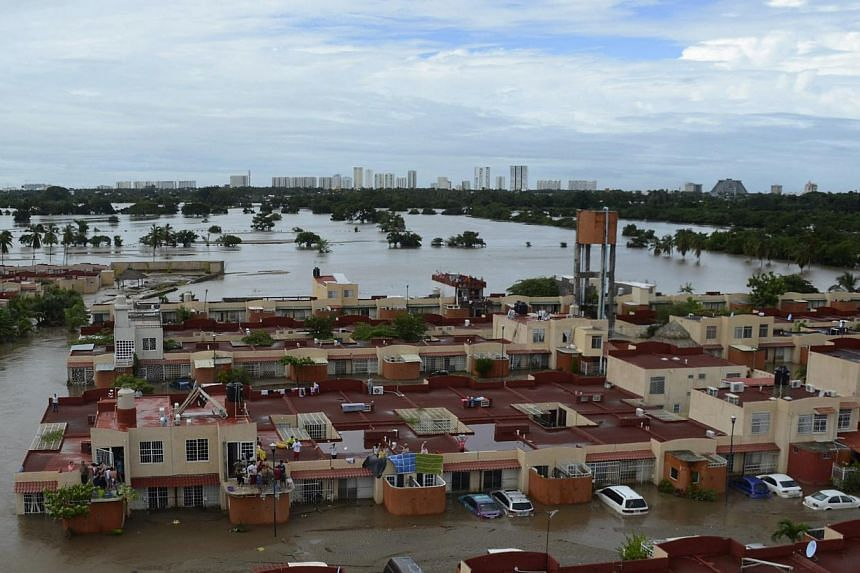 People stand on the rooftop of a home in a flooded neighborhood after Tropical Storm Manuel pounded Acapulco, Mexico, Tuesday, Sept. 17, 2013.Mexican authorities scrambled Tuesday to launch an air lift to evacuate tens of thousands of tourists