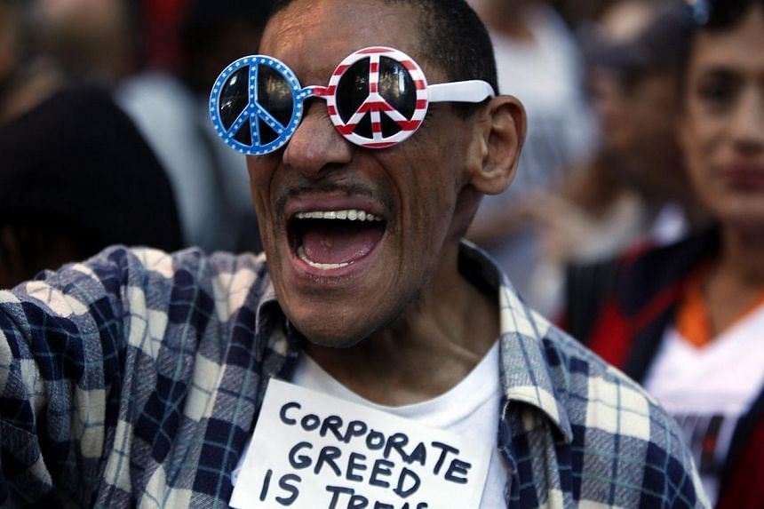 """An Occupy Wall Street protester chants slogans along 47th Street in New York September 17, 2013.""""Occupy Wall Street"""" returned to the streets of New York on Tuesday to mark the second anniversary of the birth of the social protest movement. -- P"""
