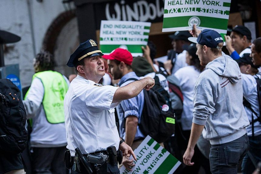 """A police officer monitors Occupy Wall Street protesters as they march from the United Nations building to Bryant Park on September 17, 2013 in New York City.""""Occupy Wall Street"""" returned to the streets of New York on Tuesday to mark the second"""