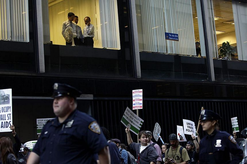 """Workers from the Bank of India watch from a window as Occupy Wall Street protesters march 47th Street in New York September 17, 2013.""""Occupy Wall Street"""" returned to the streets of New York Tuesday to mark the second anniversary of the birth of"""