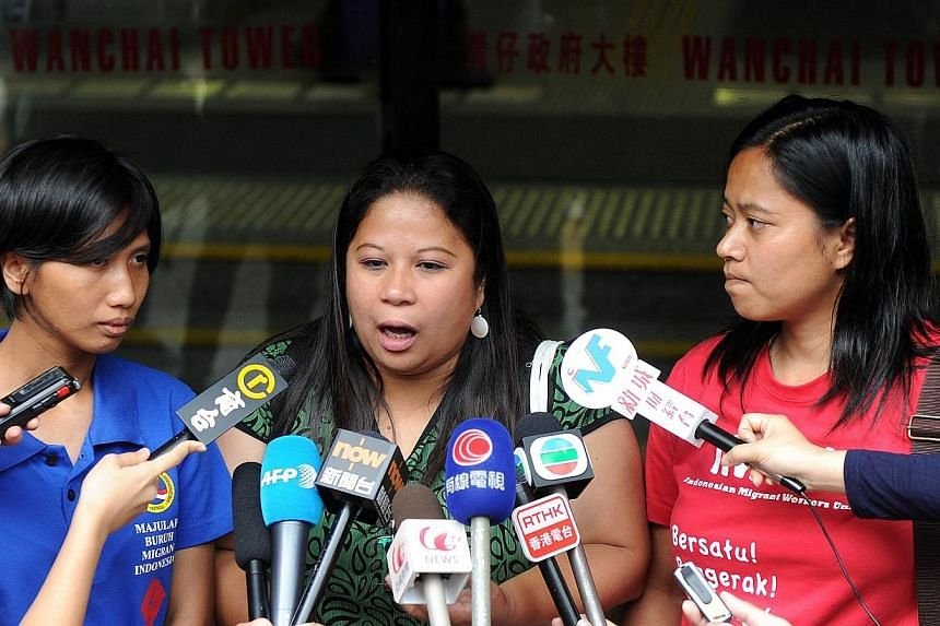 Dolores Balladares (centre), Asian Migrants Coordinating Body spokeswoman, addresses the media outside a court where a local couple stands trial for abusing their Indonesian domestic helper. -- PHOTO: AFP