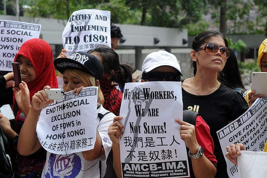 Members of the Asian Migrants Coordinating Body hold a protest outside a court where a local couple stands trial for abusing their Indonesian domestic helper in Hong Kongon Sept 18, 2013-- PHOTO: AFP