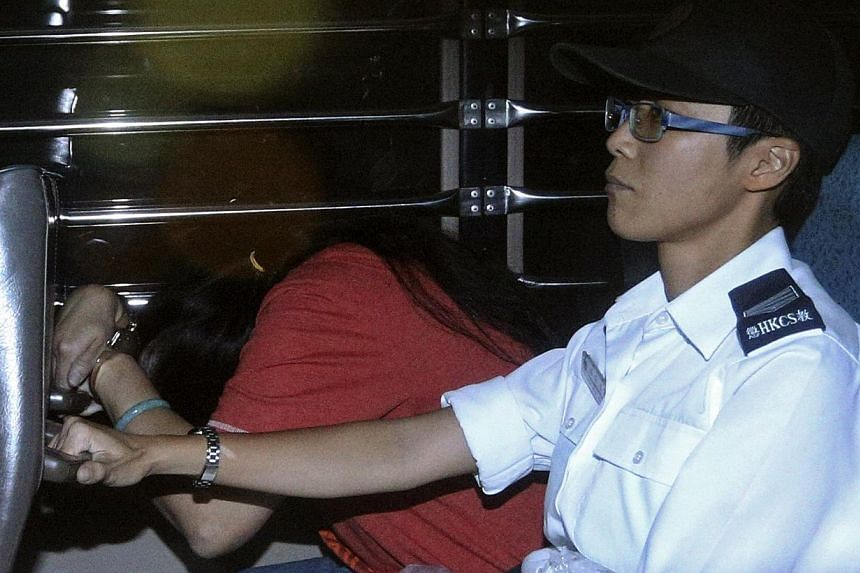 Catherine Au Yuk-shan (left), 41, a public hospital assistant, is escorted by a Hong Kong Correctional Services Department officer inside a van leaving Wanchai District Court for jail, in Hong Kong on Wednesday, Sept 18, 2013.Au and her husband