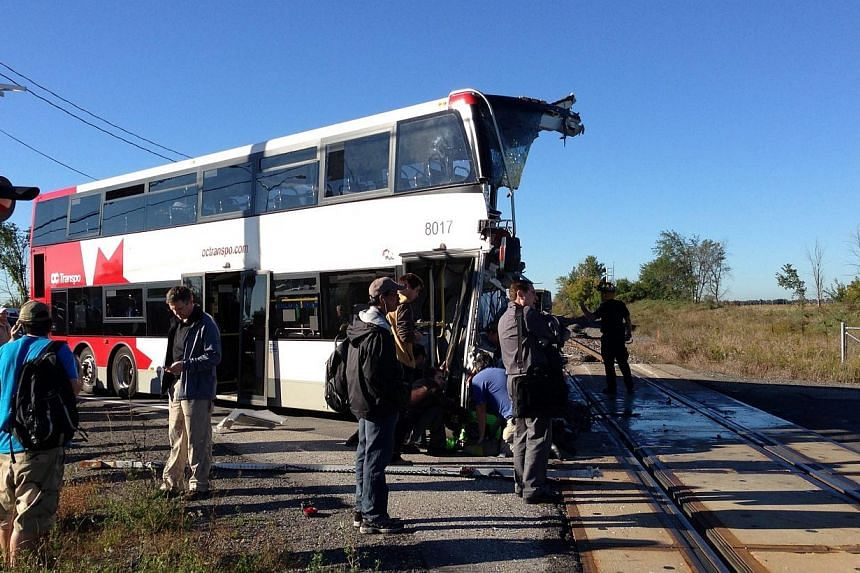 Officials respond to the scene where a city bus collided with a Via Rail passenger train at a crossing in Ottawa, Ontario on Wednesday, Sept. 18, 2013.-- PHOTO: AP