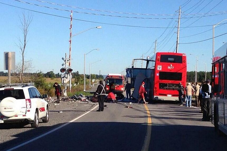 Officials respond to the scene where a city bus collided with a Via Rail passenger train at a crossing in Ottawa, Ontario on Wednesday, Sept. 18, 2013.-- PHOTO: REUTERS