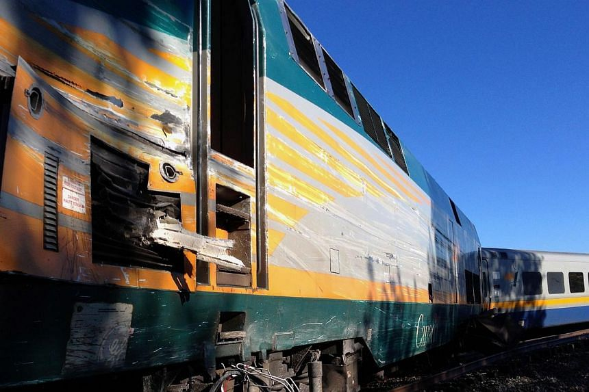 A Via Rail passenger train sits on the tracks at a crossing in Ottawa, Ontario, after a collision with a city bus on Wednesday, Sept. 18, 2013. -- PHOTO: AP