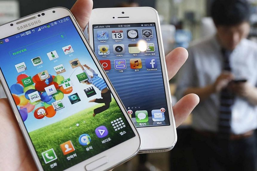 Samsung Electronics' Galaxy S4 (left) and Apple's iPhone 5 are seen in this picture illustration taken in Seoul in this file photo from May 13, 2013. A US judge ordered a new trial for November to review a portion of the damages tossed out in the lan