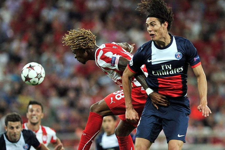 Paris Saint-Germain's Edinson Cavani (right) jumps to head the ball with Olympiakos' Gaetan Bong during the Champions League group C football match between Olympiakos and Paris Saint-Germain at the Karaiskaki stadium in Athens on Sept 17, 2013. An ut