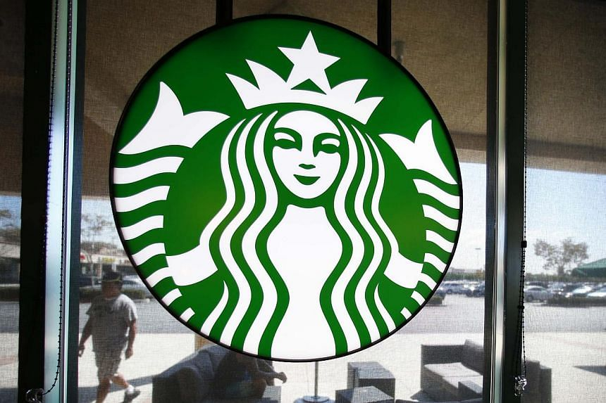 A Starbucks logo hangs on a window at a newly designed Starbucks coffee shop in Fountain Valley, California on Aug 22, 2013. Starbucks Corp Chief Executive Howard Schultz requested on Tuesday that the coffee chain's customers leave their firearms at